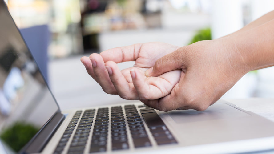 Woman holding and pressing or touching her hand while working with laptop in the office. Numbness or pain on hand concept.