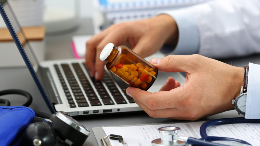 Male medicine doctor hands hold jar of pills