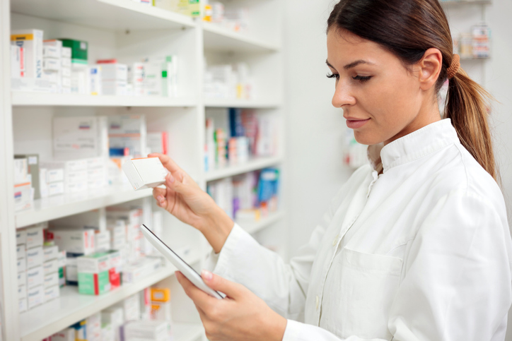 Serious young female pharmacist using tablet