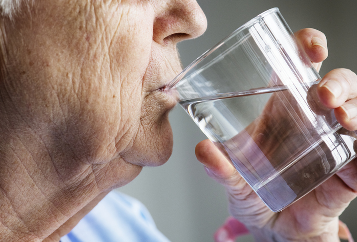Side view of elderly woman drinking water