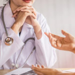 female doctor listening to depressed patient talking at hospital