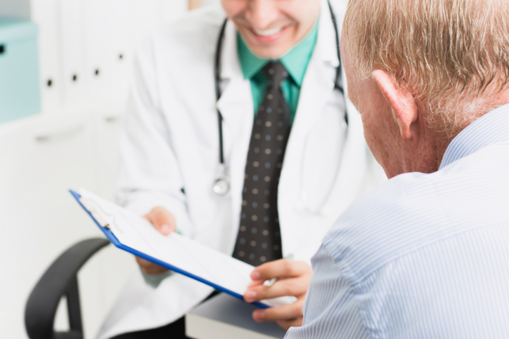 Smiling doctor consulting with senior male patient