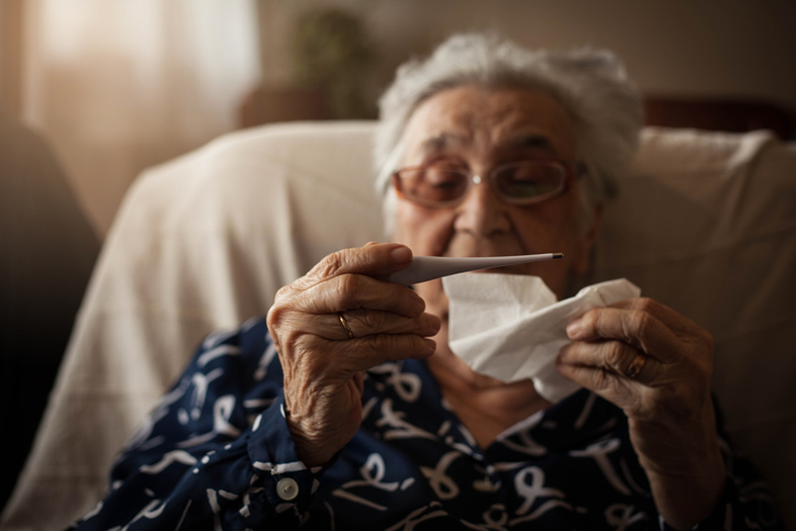 Senior woman checking body temperature with thermometer and blowing nose