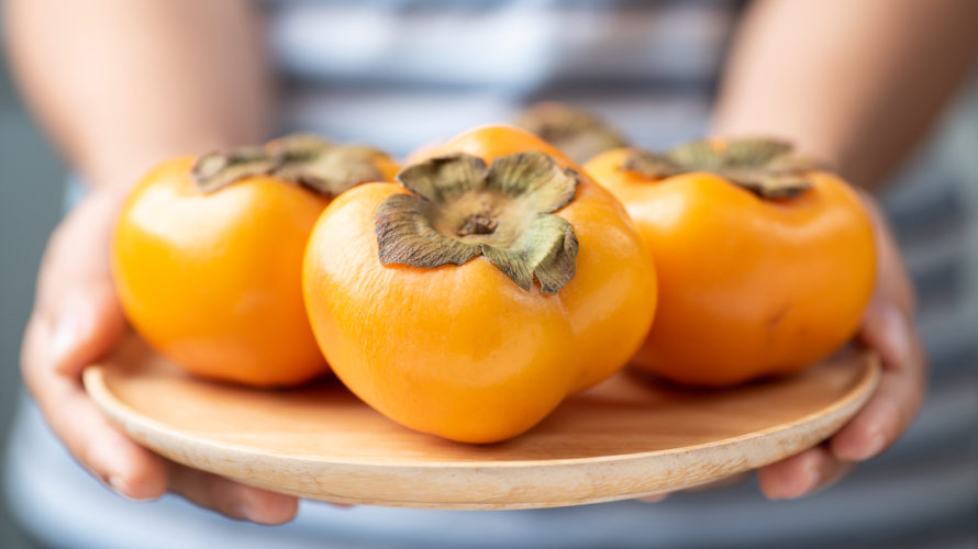 Persimmon fruit holding by hand