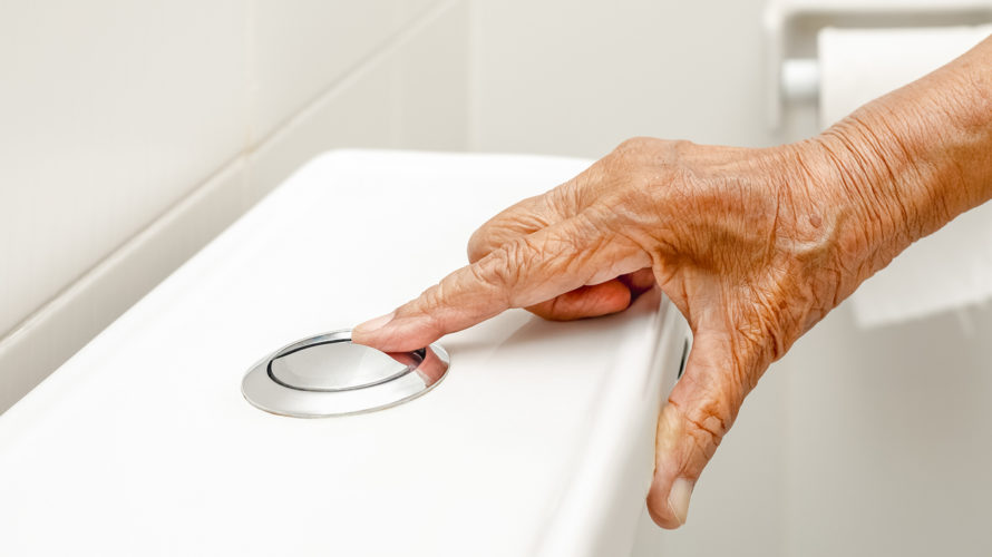 Elderly woman hand flushing toilet