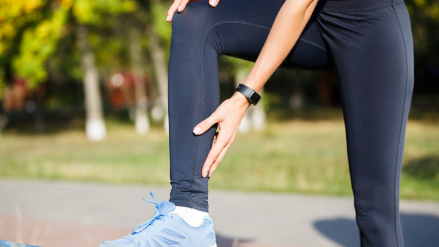 Female runner touching cramped calf at jogging