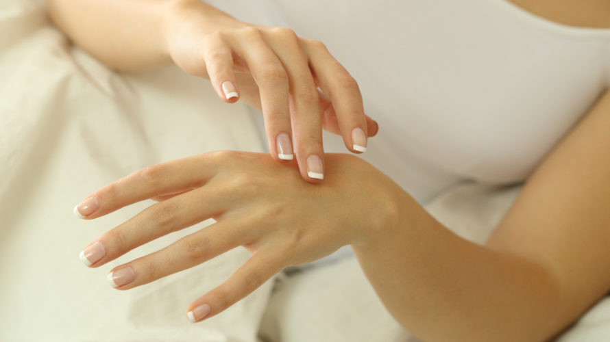 Woman hands rubbing moisturizer cream