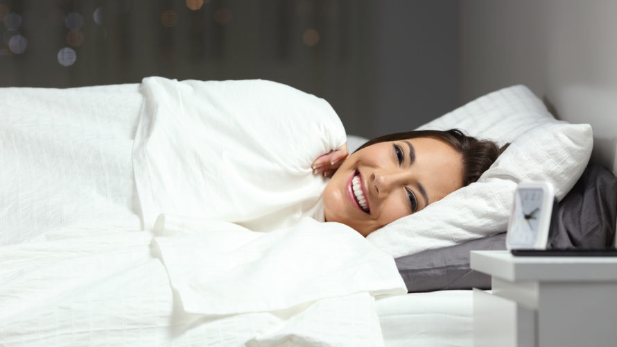 Happy woman in the bed looking at camera in the night