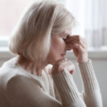 Fatigued upset older woman massaging nose bridge feeling eye strain