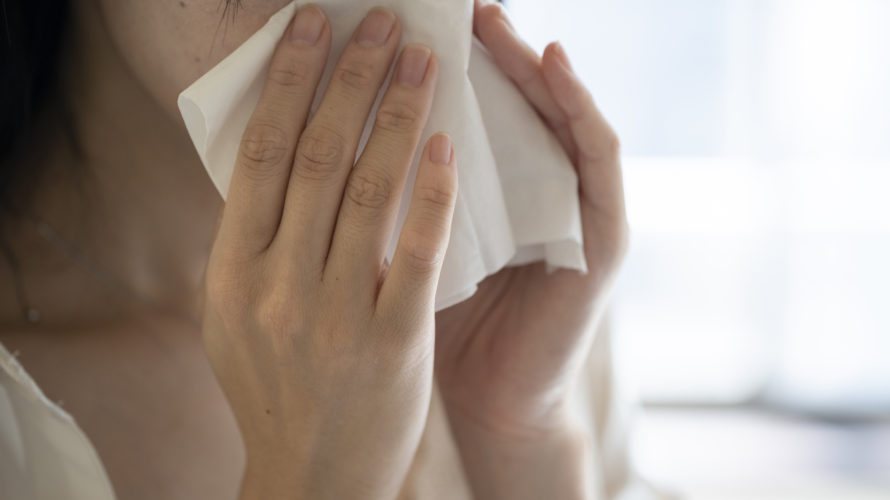 Hand of woman blowing nose with tissue