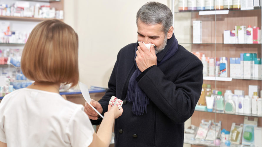 Ill man covering mouth with tissue in drugstore.
